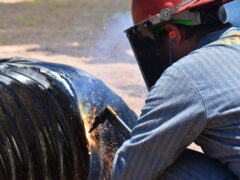 A woman welds cut in a pipe.