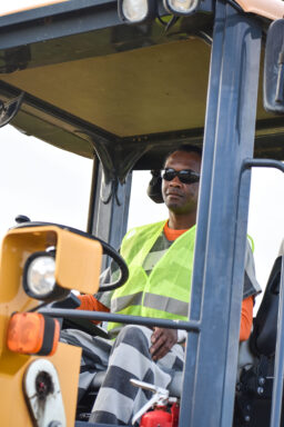 A black male with sunglasses on in an inmate uniform drivers a front-end loader.