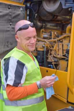White male with sunglasses on in an inmate uniform checks the oil in an excavator