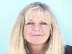 Mug shot of a white woman with blonde hair in her 50's smiling wearing a navy blue jump suit.