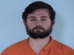 Mug shot of a white male wearing an orange jumpsuit with a beard.
