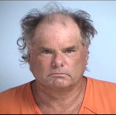 Mug shot of a white male in his 50's wearing an orange jumpsuit.