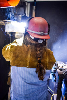 A woman with a long braid welds with a helmet.