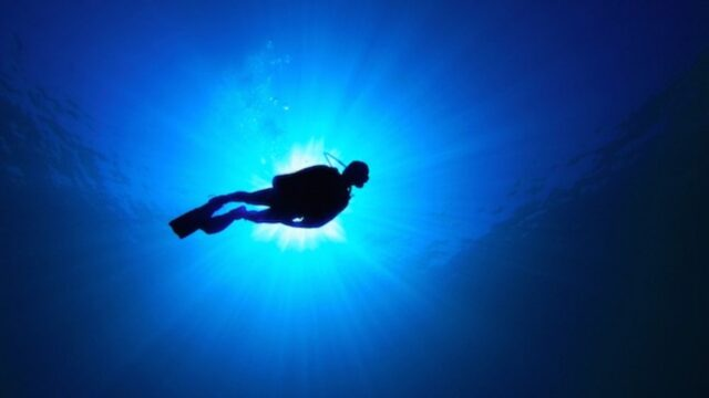 A silhouette of a diver from the bottom of the ocean looking up to the surface.