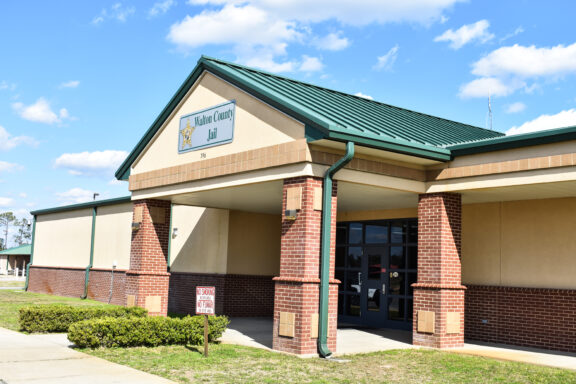 """A brick building with a green roof with a sign that reads, """"Walton County Jail""""."""