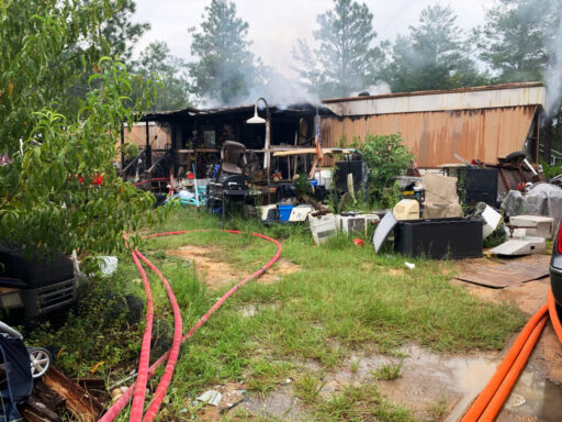 Single wide mobile home with smoke coming from inside the home