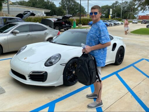 A white male in a blue shirt holding a backpack. In the backround is a white Porsche Turbo.