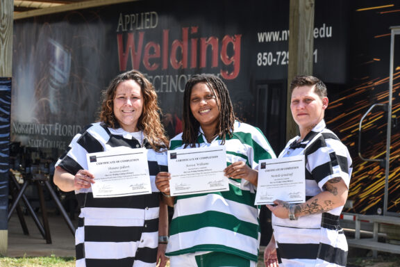 A group of three female inmates stand and smile as they hold certificates.