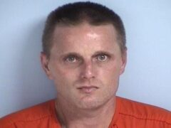 Mug shot of a white male in an orange jumpsuit.