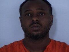 Mug shot of a black male in an orange jumpsuit.