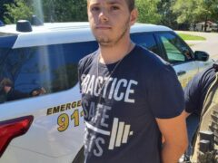 White male with bleached blond hair and navy blue shirt with his hands cuffed behind his back.