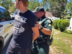 White male in a navy blue shirt being cuffed by Walton County Sheriff's Office deputy