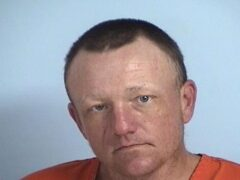 Mug shot of a white male in an orange jumpsuit.