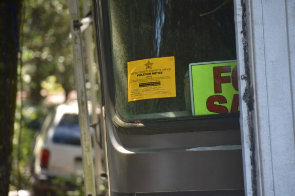 A yellow sticker on the windshield of a dilapidated camper.