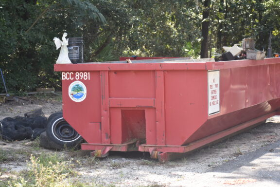 a dumpster. with a Walton County seal on the side of it.
