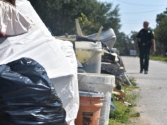 A sheriff deputy walking alongside a pile of trash on the right-of-way
