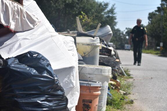 A sheriff deputy walking alongside a pile of trash on the right-of-way