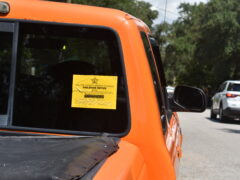 A yellow violation sticker on the back windshield of an orange truck.