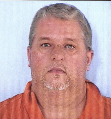 Mug shot of a white male with a gray and white goatee with an orange jumpsuit.