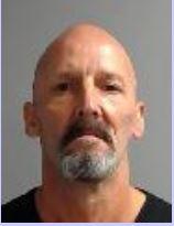 Mug shot of a bald white male with a black and grey goatee