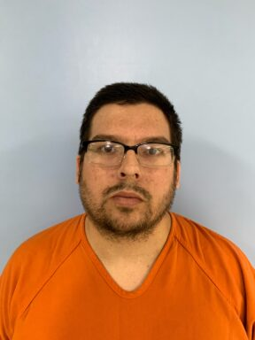 Mug shot of a white male with dark hair and black glasses