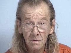 Mug shot of an older white male with glasses and long grayish blonde hair