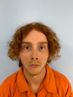 Mug shot of a white. male with red curly hair