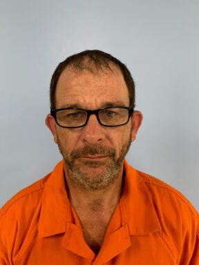 Mug shot of a white male with black glasses