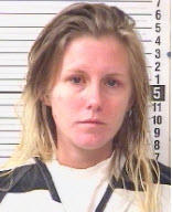 Mug shot of a white female and blonde hair wearing black and white jumpsuit