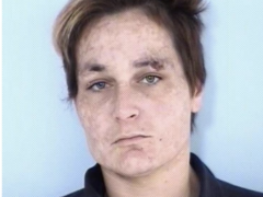 Mug shot of a white female with short brown hair and a sore above her eye wearing a navy blue jumpsuit