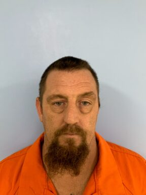 Mug shot of a white male with brown hair and a long goatee wearing an orange jumpsuit