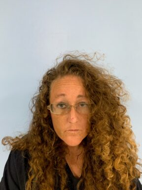 Mug shot of a white female with curly red hair and glasses
