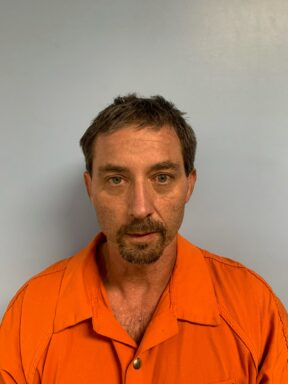 Mug shot of a white male with brown hair and goatee wearing an orange jumpsuit