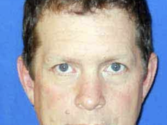 Mug shot of a white male with red hair and blue eyes