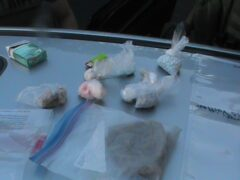 Multiple baggies with unknown pills sitting on the hood of a vehicle.