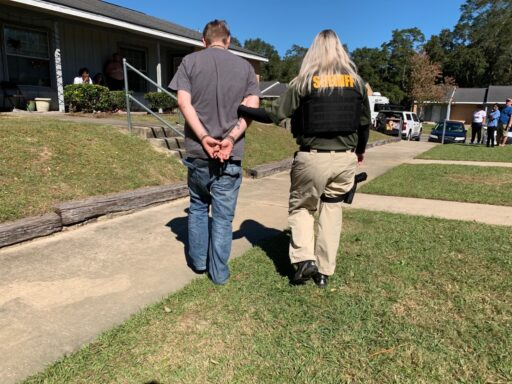 A female deputy with a bullet-proof vest walks a white male in handcuffs along a sidewalk in front of an apartment complex.
