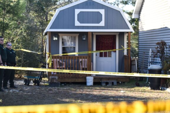 Crime Scene tape in front of a small shed.
