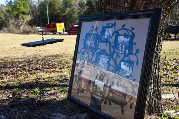 Large picture frame with family photos leaned up against a tree next to a rope swing