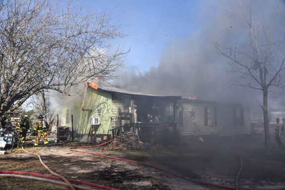 Firefighters spraying water on fire that is coming from the roof of a light green house