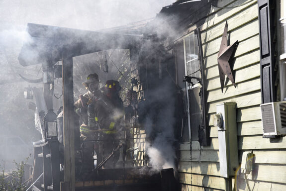 Two firefighters on the front porch of a light green home with smoke coming from the roof