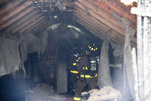 firefighters in damaged, smoke-filled room of a home