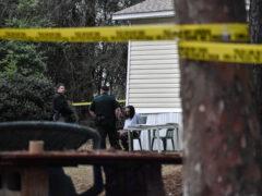 Handcuffed suspect sits cuffed between two deputies
