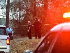 Deputies stand btween crime scene tape on a homicide call