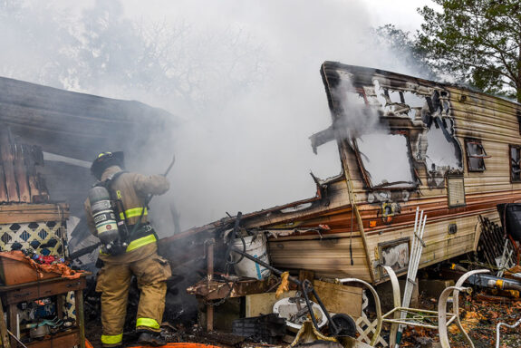 firefighter using tool inside smoke-filled camper