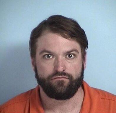 Mug shot of a white male with dark brown facial hair wearing an orange jumpsuit