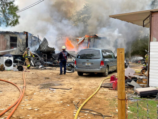 Firefighters in front of burning mobile home