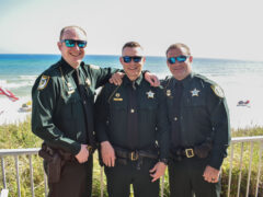 Three deputies in uniform smiling in front of the beach.