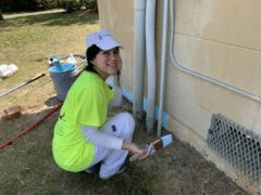 A female wearing a bright yellow tshirt and white ball cap uses blue paint to prime the side of a building
