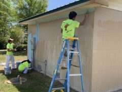 API Coating employees assist WCSO with priming the side of one of the buildings set to be the canvas for a new mural at Driftwood Estates Park