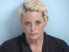 Mug shot of white woman with dyed blonde hair and dark roots